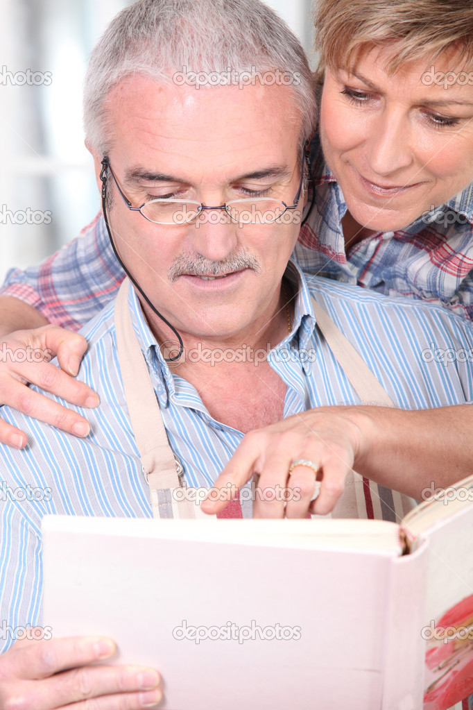 Mature couple consulting cookbook — Stock Photo #7089910
