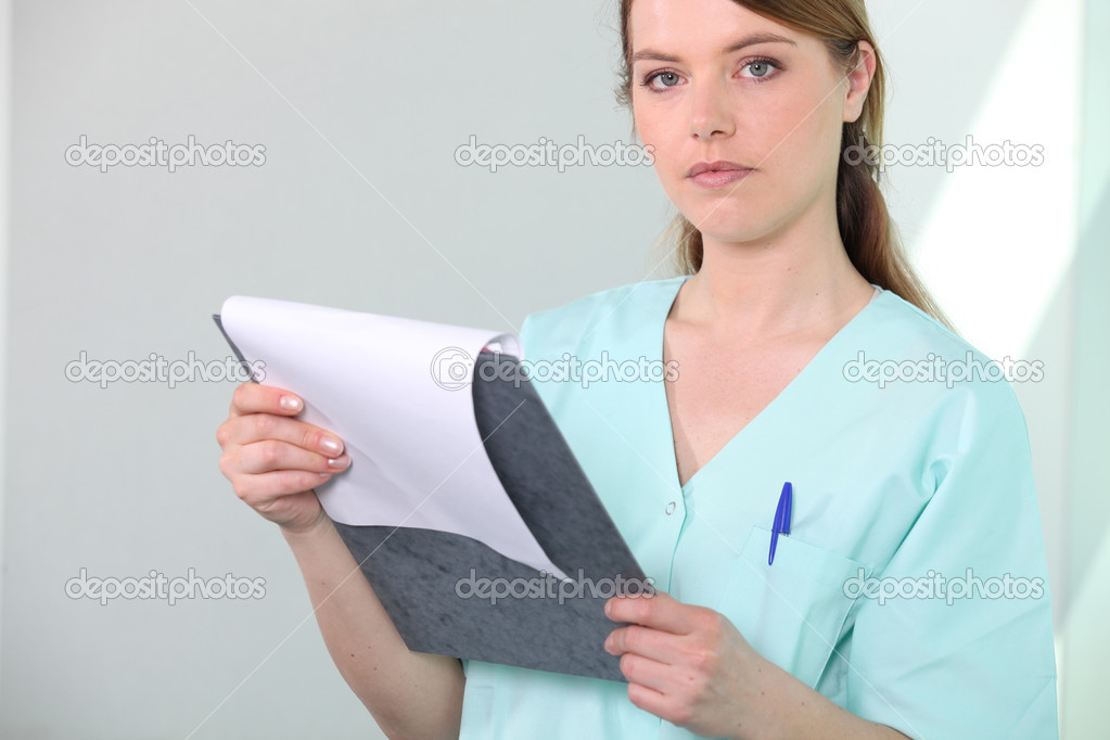 Nurse in hospital scrubs examining a clipboard — Stock Photo #7089926