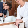 Foto Stock: Son fixing tap