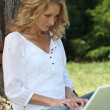 Blond woman sat by tree with laptop — Stock Photo