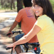 Pretty young woman and her boyfriend riding bikes through the woods — Stock Photo #7133180