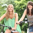 Stock Photo: Two teenage girls riding bikes in the countryside