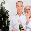 Elderly couples drinking champagne at Christmas - Stock Photo