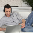 Man lying on a sofa with his laptop and a pair of headphones — Stock Photo