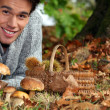 Man gathering mushrooms and chestnuts in the forest - Lizenzfreies Foto