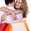 Woman with shopping bags hugging her boyfriend — Stock Photo