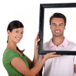 Couple holding empty picture frame — Stock Photo #7133832