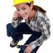 A female construction worker with a drill. — Stock Photo