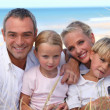 Two parents and their two children in front of the sea - Stock Photo