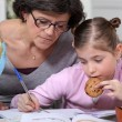 Mother helping her daughter with her homework. — Stockfoto #7134038