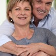 Mature married couple in a loving embrace - Stock Photo