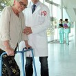 Stock Photo: Helpful doctor and senior womwith walker