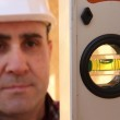 Builder knelt holding spirit level — Stock Photo #7134680