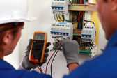 Electrician and his apprentice working on a fuse board — Stock Photo