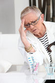 Older woman with a headache — Stock Photo