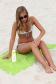 Young woman applying sunblock at the beach — Stock Photo