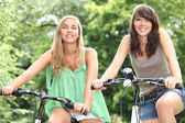 Two teenage girls riding bikes in the countryside — Stock Photo