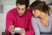 Junger mann und junge frau, die videospiele spielen — Stockfoto