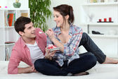 Couple eating cake in bed — Stock Photo