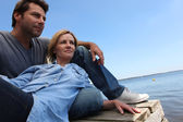 Couple lazing by the water — Stock Photo