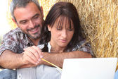 Farming couple sat with laptop computer — Stock Photo