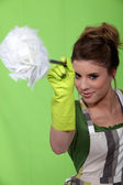Woman in green with a feather duster — Stock Photo