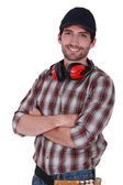 Portrait of a workman with earmuffs around his neck — Stock Photo