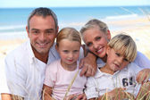Two parents and their two children in front of the sea — Stock Photo