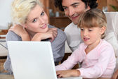 Casal com sua filha e um laptop — Fotografia Stock