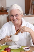 Elderly woman having breakfast — Stock Photo