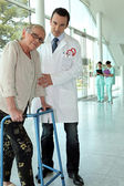 Helpful doctor and senior woman with walker — Stock Photo