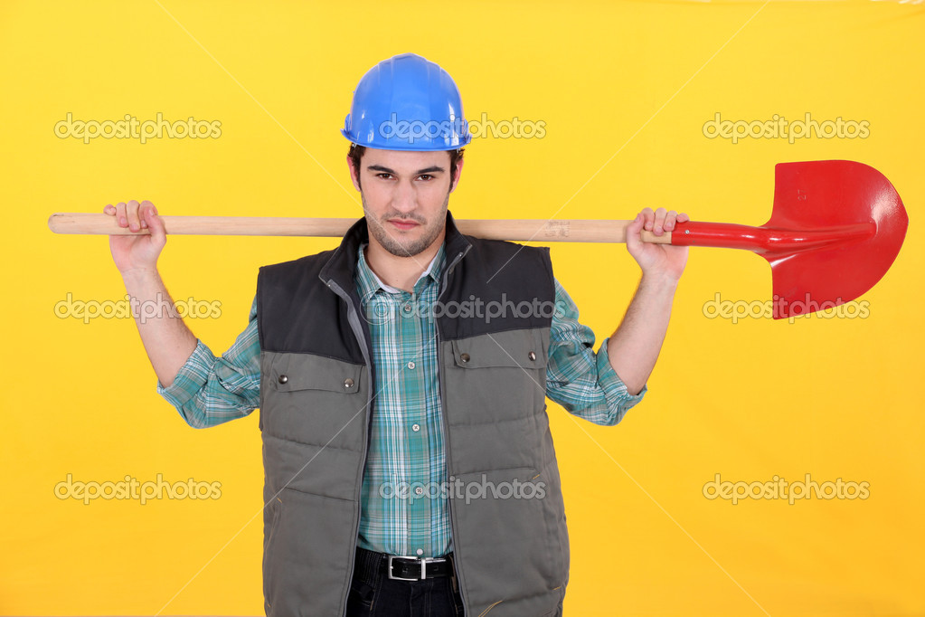 Scowling labourer carrying a shovel — Stock Photo #7132596