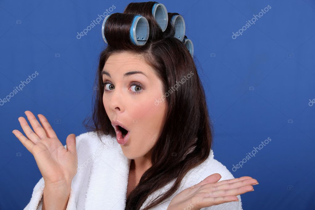 Cute brunette in bathrobe with hair curlers against blue background — Stock Photo #7133863