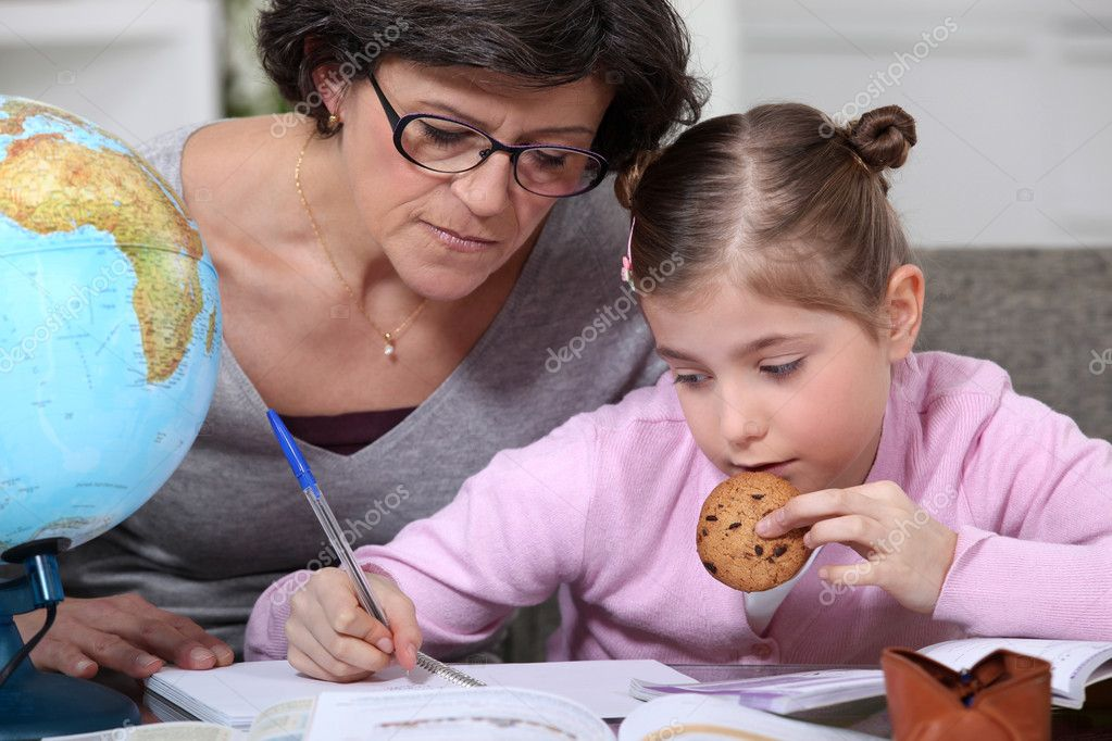 Mother helping her daughter with her homework. — Stock Photo #7134038