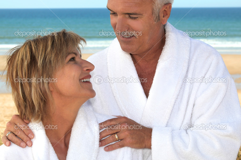 Couple wearing a bathrobe on a beach. — Stock Photo #7134266