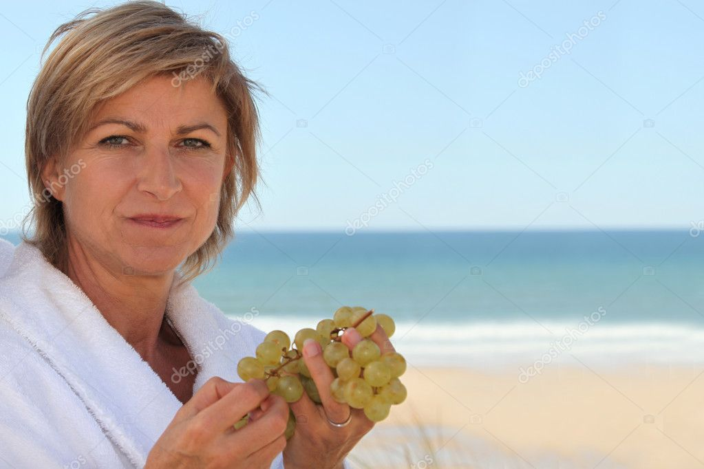 Mid aged woman eating grapes near the sea  Stock Photo #7134296