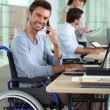 Smiling man in a wheelchair working in an office — Stock Photo