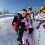 paar posiert mit Kind neben Schneemann im Mountain resort — Stockfoto