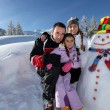 Couple posing with child beside snowman at mountain resort — Stock Photo