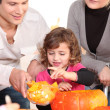 Stock Photo: Family carving hallowe'en pumpkin