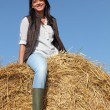 Stock Photo: Female cultivator posing on hay bale