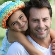 Stock Photo: Father carrying daughter on back