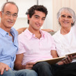 Grandparents and grandson skimming through album — Stock Photo #7230834