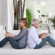 Mature couple sitting back to back on a sofa with laptop computers — Stock Photo