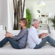 Mature couple sitting back to back on a sofa with laptop computers — Stock Photo #7230909