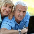 Portrait of smiling mature couple with laptop outdoors — Stock Photo