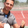 Male tennis player with bottle of water and towel — Foto Stock