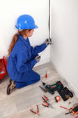 Female electrician installing a wall socket — Stock Photo