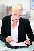 Businesswoman writing in a leather bound agenda — Stock Photo
