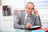 Older businessman using a cellphone — Stock Photo